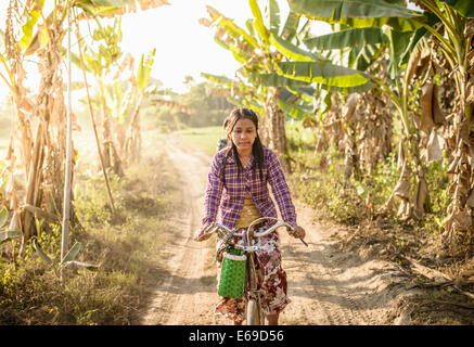 Asian woman riding bicycle on rural road - Stock Image