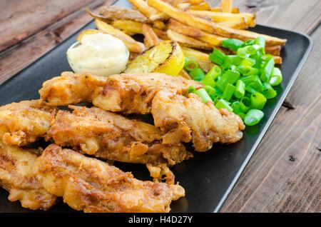Poisson et frites avec de la mayonnaise maison sur plaque noire - Image