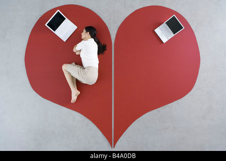 Woman lying on the ground with laptop on large broken heart, abandoned laptop behind her - Stock Image