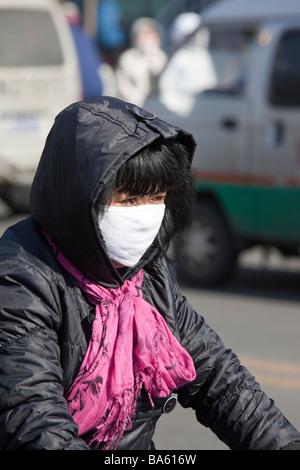 Une femme portant un masque pour lutter contre la pollution de l'air dans la ville de suihua en Chine du Nord - Image