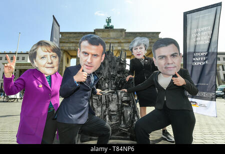 Berlin, Germany. 11th May, 2019. Activists with masks of the European politicians Angela Merkel (l-r, Chancellor of Germany), Emmanuel Macron (President of France), Theresa May (Prime Minister of Great Britain) and Pedro Sanchez (Acting Prime Minister of Spain) stand in front of the Brandenburg Gate during an art action of the 'Aktion Aufschrei - Stoppt den Waffenhandel! They protest against arms exports to war-participants in Yemen on a 'weapons throne' modelled on the 'Iron Throne' from Games of Thrones. Credit: Jens Kalaene/dpa-Zentralbild/dpa/Alamy Live News - Stock Image