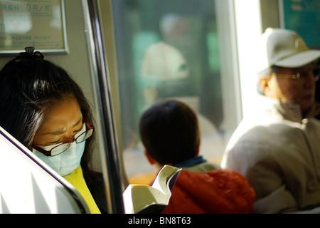 Banlieue sur le réseau de transport de tokyo portant un masque pour aider à prévenir la propagation des germes et se protéger contre - Image