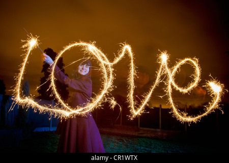 Woman writing LOVE with sparkler - Stock Image