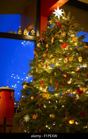 Beautiful Christmas Tree Under High Roof. Holidays Christmas Theme. Vertical Photography. - Stock Image
