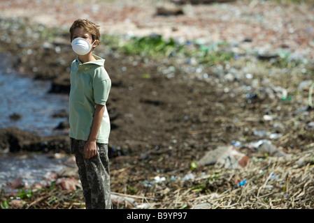 Garçon debout sur un rivage pollué, portant un masque de pollution - Image