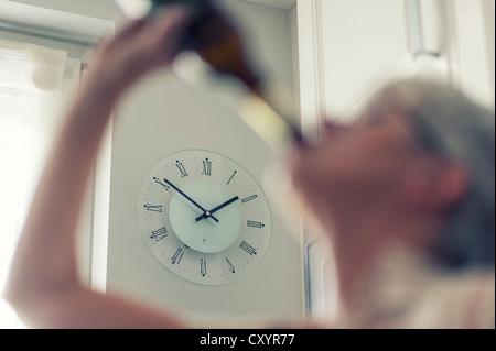 Femme dépendante de l'alcool, alcoolique, buvant une bouteille de bière en plein jour - Image