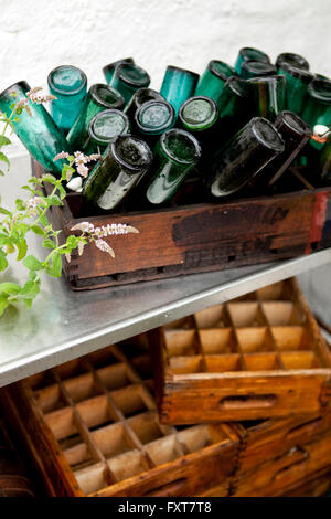 Wooden crate with upside down vintage bottles on terrace in rain - Stock Image