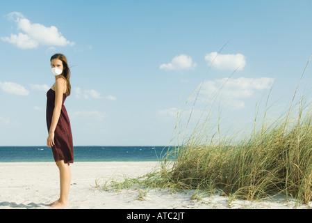 Femme debout sur la plage avec masque de pollution, tournant le visage vers la caméra - Image