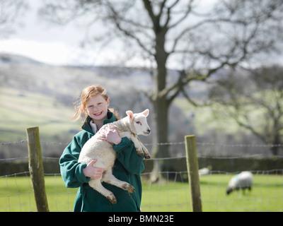 Child holding lamb smiling - Stock Image