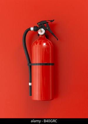 Red fire extinguisher on red background - Stock Image