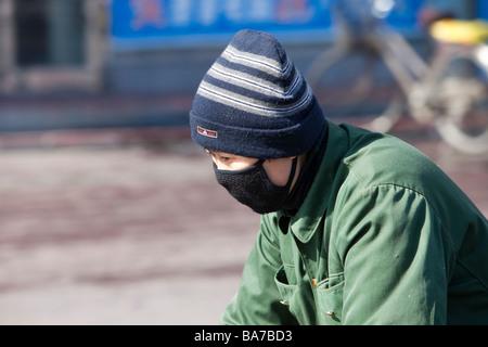 Un homme portant un masque pour lutter contre la terrible pollution de l'air dans la ville de suihua en Chine du Nord - Image