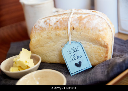 Loaf of bread with butter on cloth - Stock Image