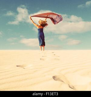 Rear view of a woman holding a scarf that's blowing in the wind - Stock Image