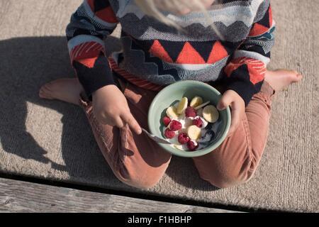 Boy holding bowl of fruit, high angle - Stock Image