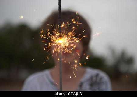 Thirteen year old boy holds up a large spakler on the fourth of July. - Stock Image