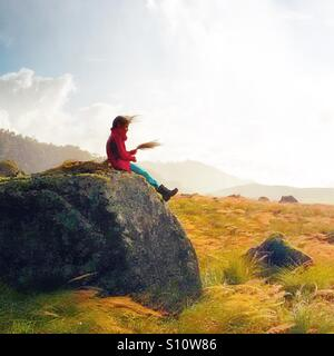 Kid sitting on a wind blown rock in an old lava flow at the base of Volcan Baru in the republic of Panama. - Stock Image