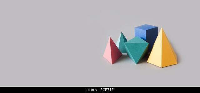 Solides platoniques colorés, figures géométriques abstraites sur fond gris. Pyramid prism cube rectangulaire jaune bleu rose vert formes colorées. Faible profondeur de champ, espace copie. - image d'archive