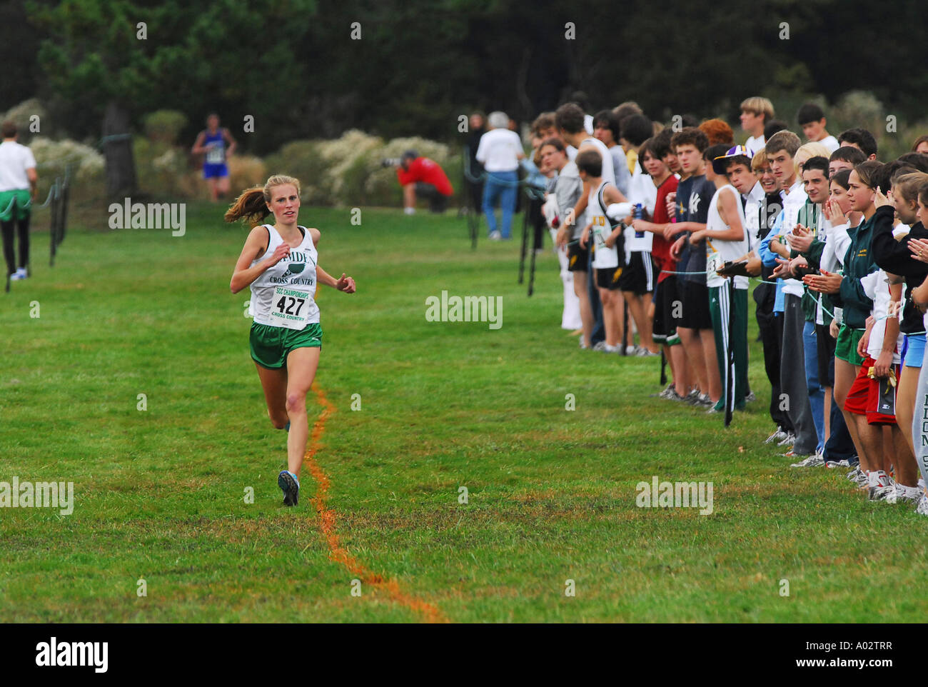 A lone runner makes her way past the cheering crowds during a Cross Country Event - Stock Image