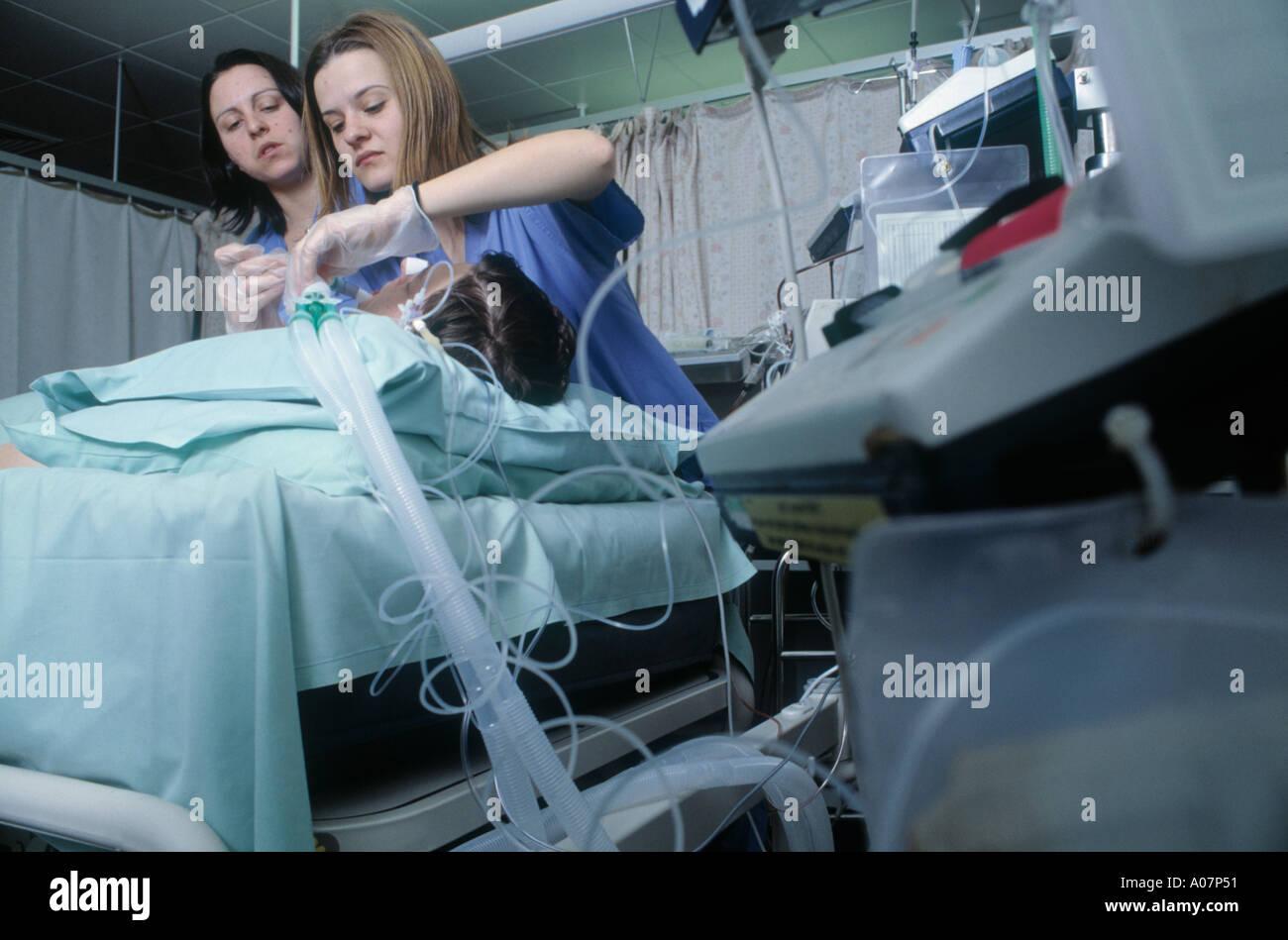 Spanish Nurses put a patient on oxygen in intensive care unit NHS hospital Blackburn, UK Stock Photo