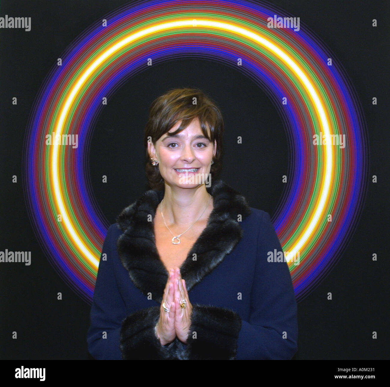 Cherie Blair, with her hands together in a mock praying gesture, standing in front of a halo like work of art Stock Photo