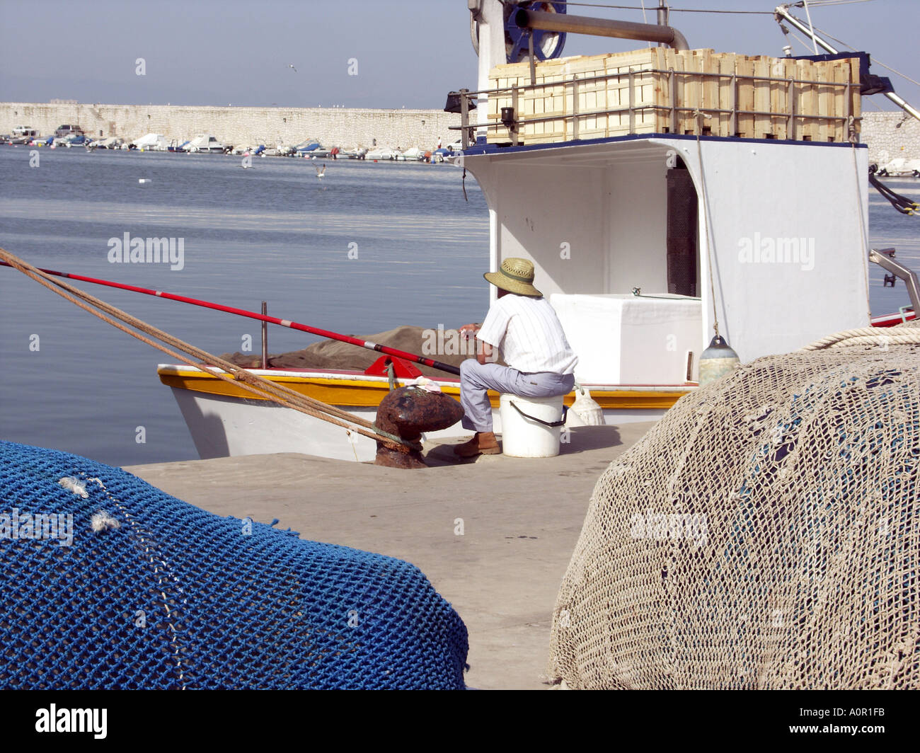 Angler Fishing with Rod and Line next to a Commercial Fishing Boat, Puerto Deportivo de Fuengirola, Fuengirola Port, - Stock Image