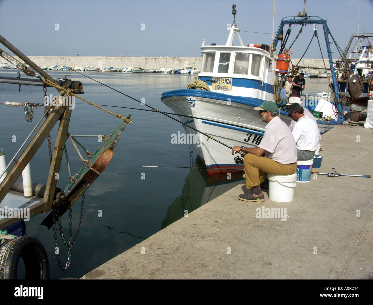 Three Anglers Fishing with Rod and Line next to a Commercial Fishing Boat, Puerto Deportivo de Fuengirola, Fuengirola, - Stock Image