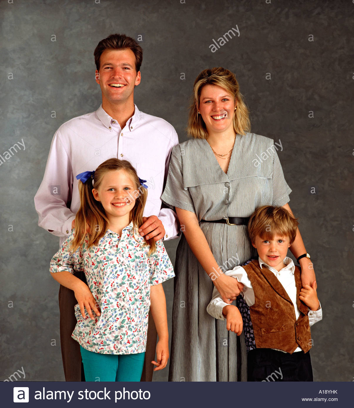 white middle class nuclear family posing for studio photo stock