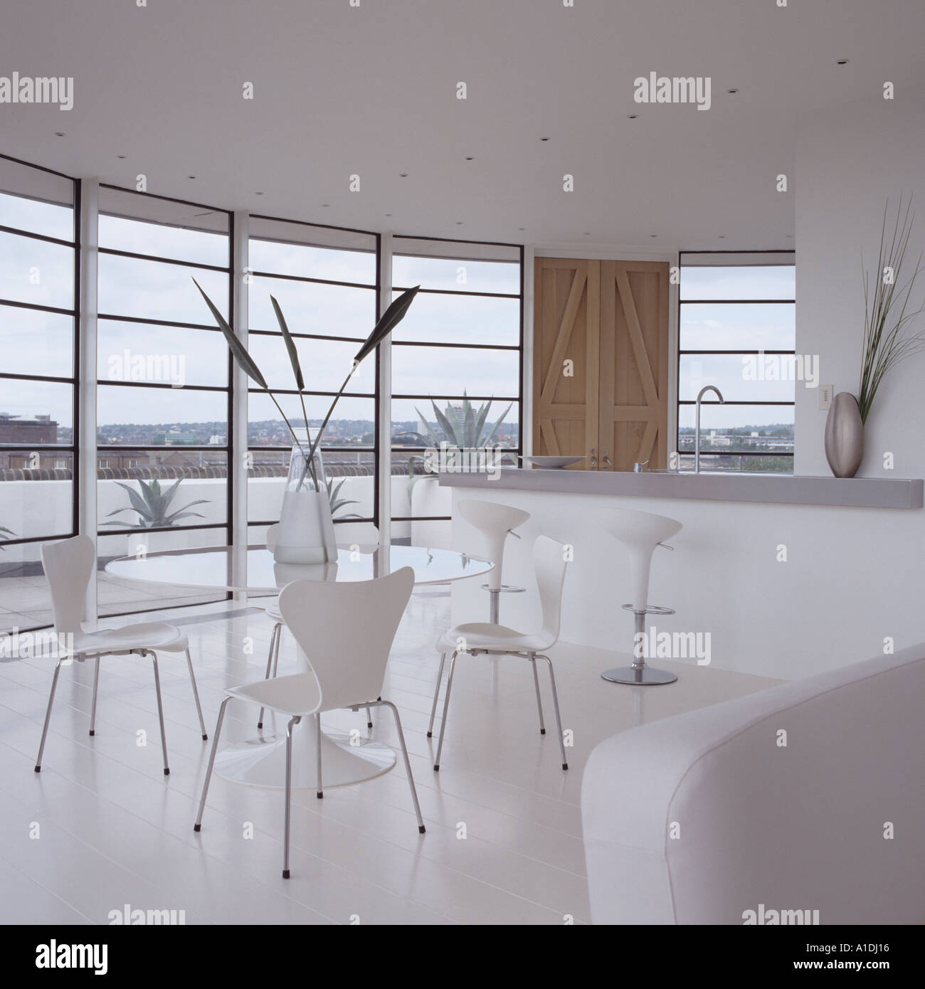 Dining area with modern furniture in round white penthouse in london