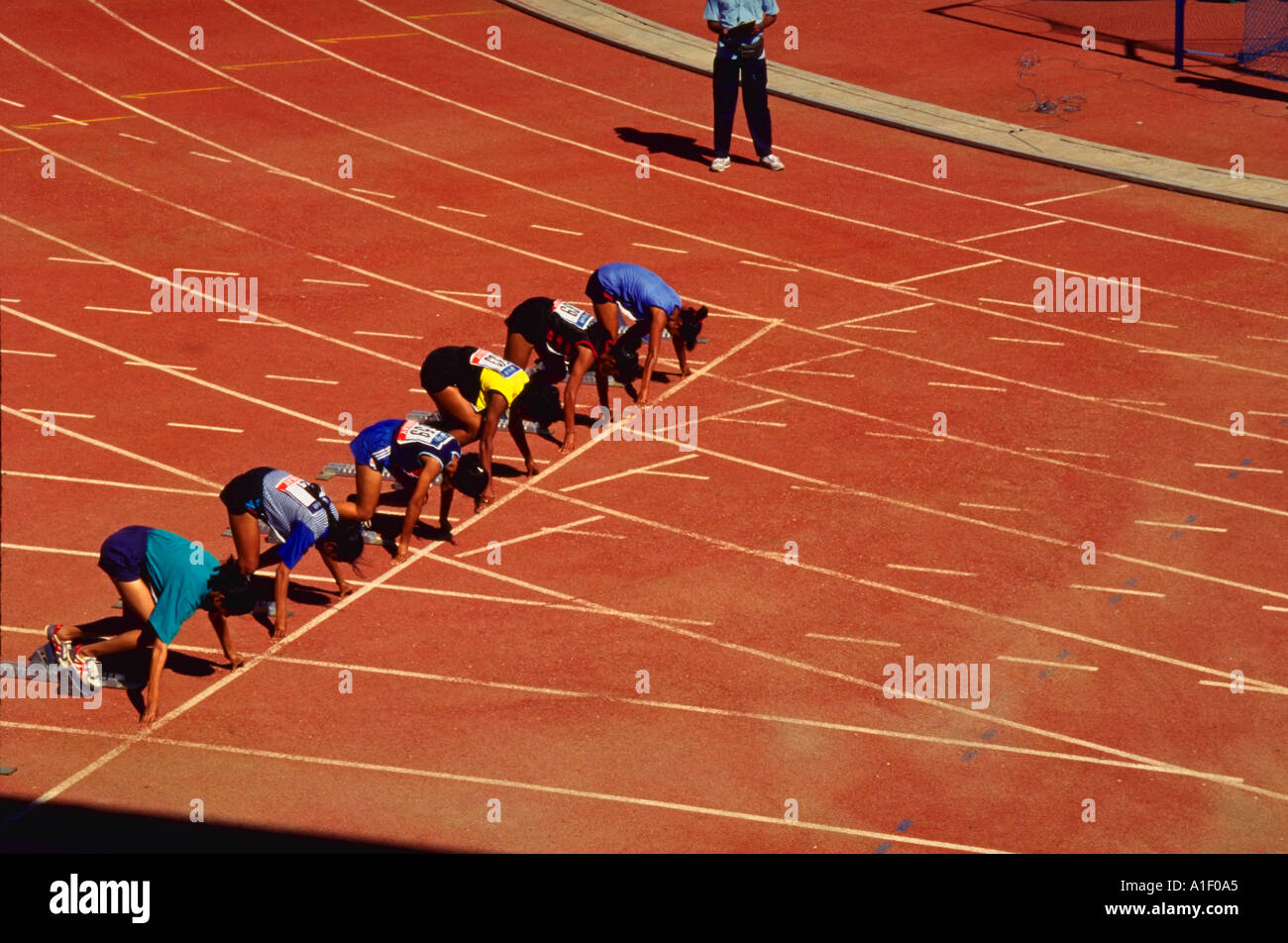 group of runners in starting position at starting line on track