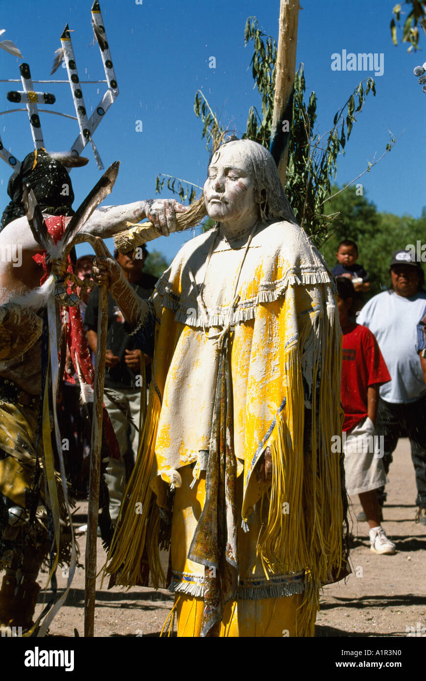 Apache girl is painted with sacred clay and corn meal during
