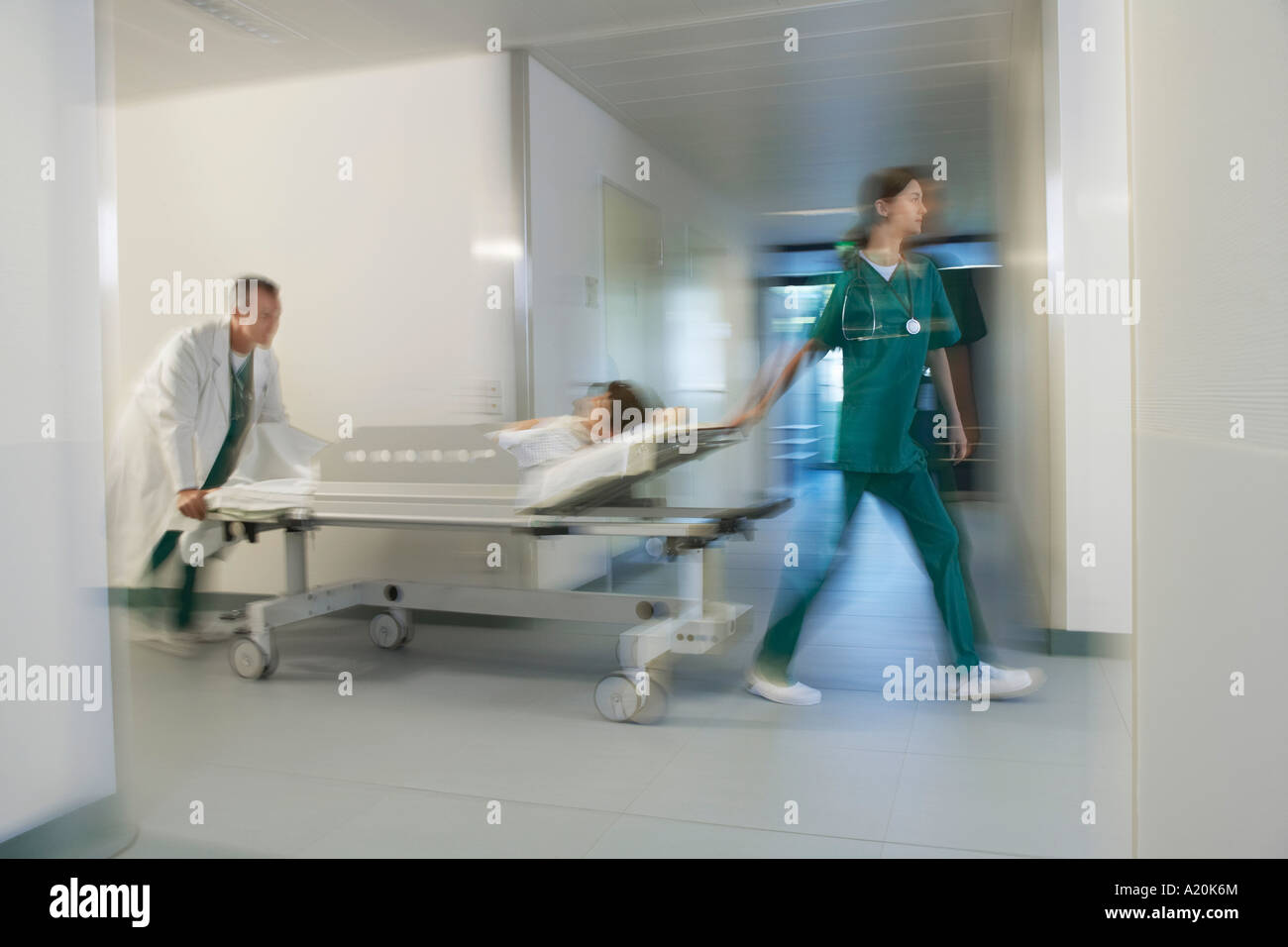 Medical Workers Moving Patient on gurney through hospital corridor, motion blur - Stock Image