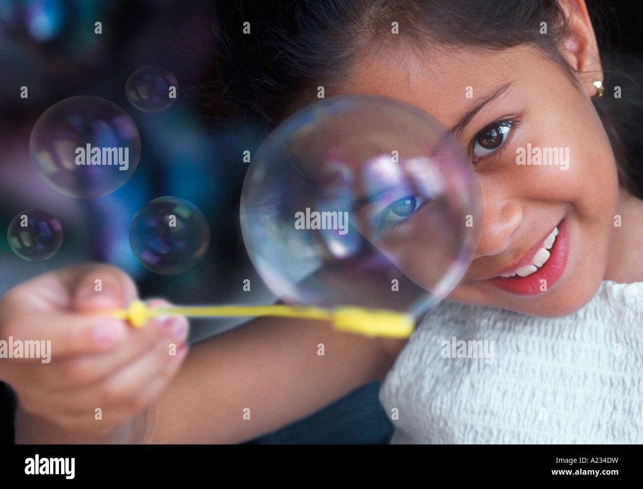 Pretty Young Girl Playful Playing Games Smiling Blowing Bubbles Sandra Baker - Stock Image