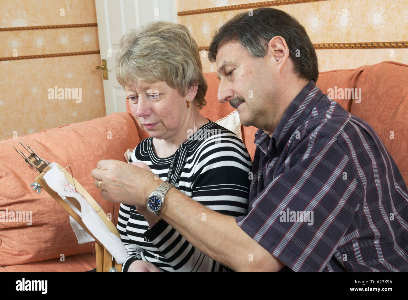 husband helping his wife with cross stitch after suffering a stroke - Stock Image