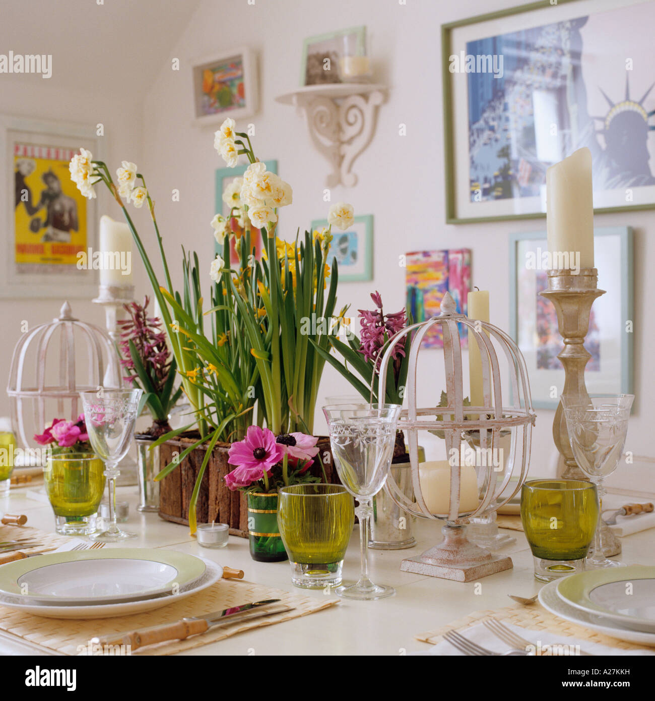 Set table decorated with daffodils and candles in London townhouse - Stock Image