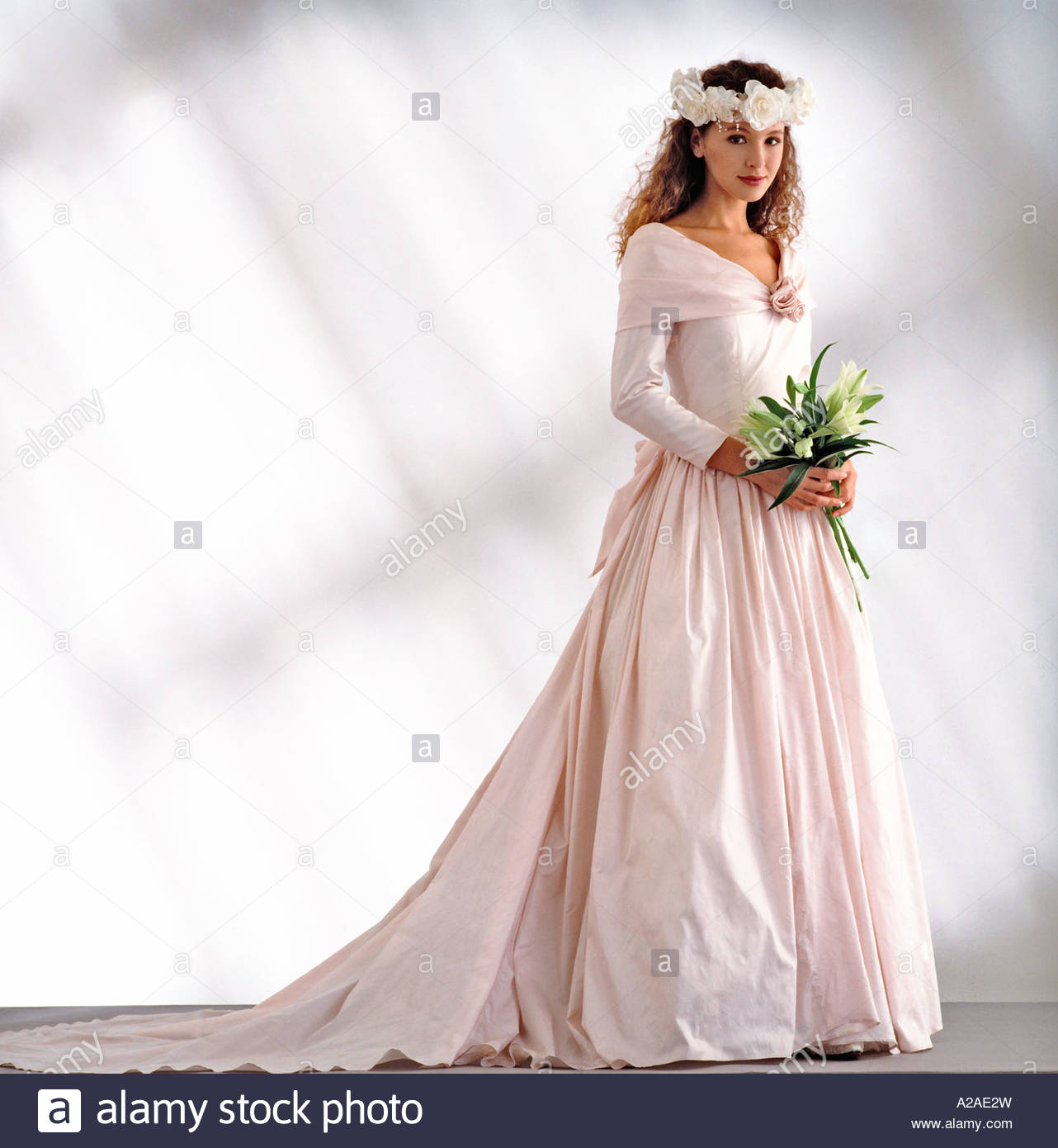 Pretty young bride stands ready in a pale pink wedding dress ...