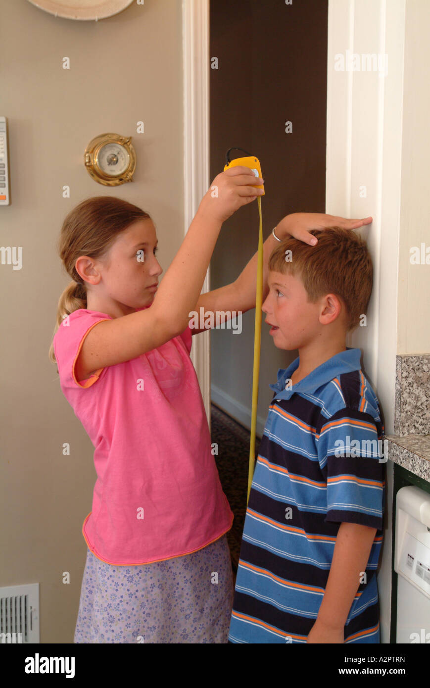 10-year-old-girl-uses-a-measuring-tape-to-see-how-tall-her-7-year-A2PTRN.jpg