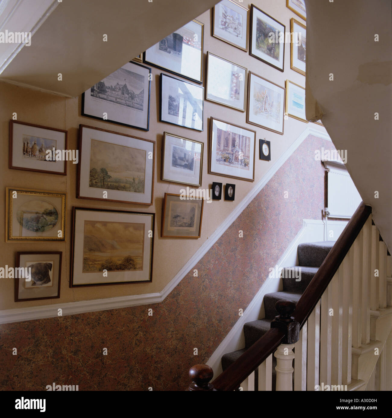 Staircase and wall of pictures and artwork - Stock Image
