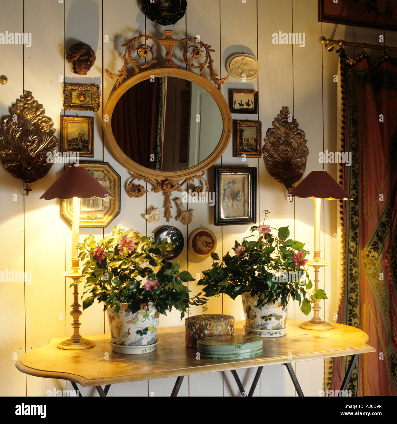 Mirror and artwork above console table with flower arrangement and