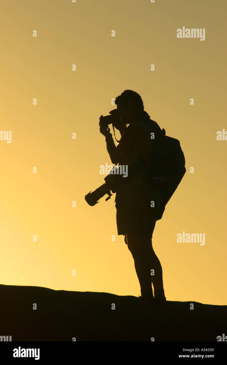 A working photographer shoots sunset over a sand dune in Moon Valley, Atacama Desert, Chile - Stock Image