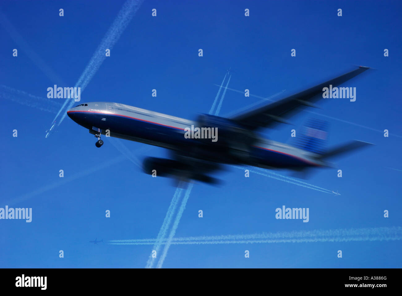 Commercial airplane in flight with many other airlineres above passing at high altitude - Stock Image