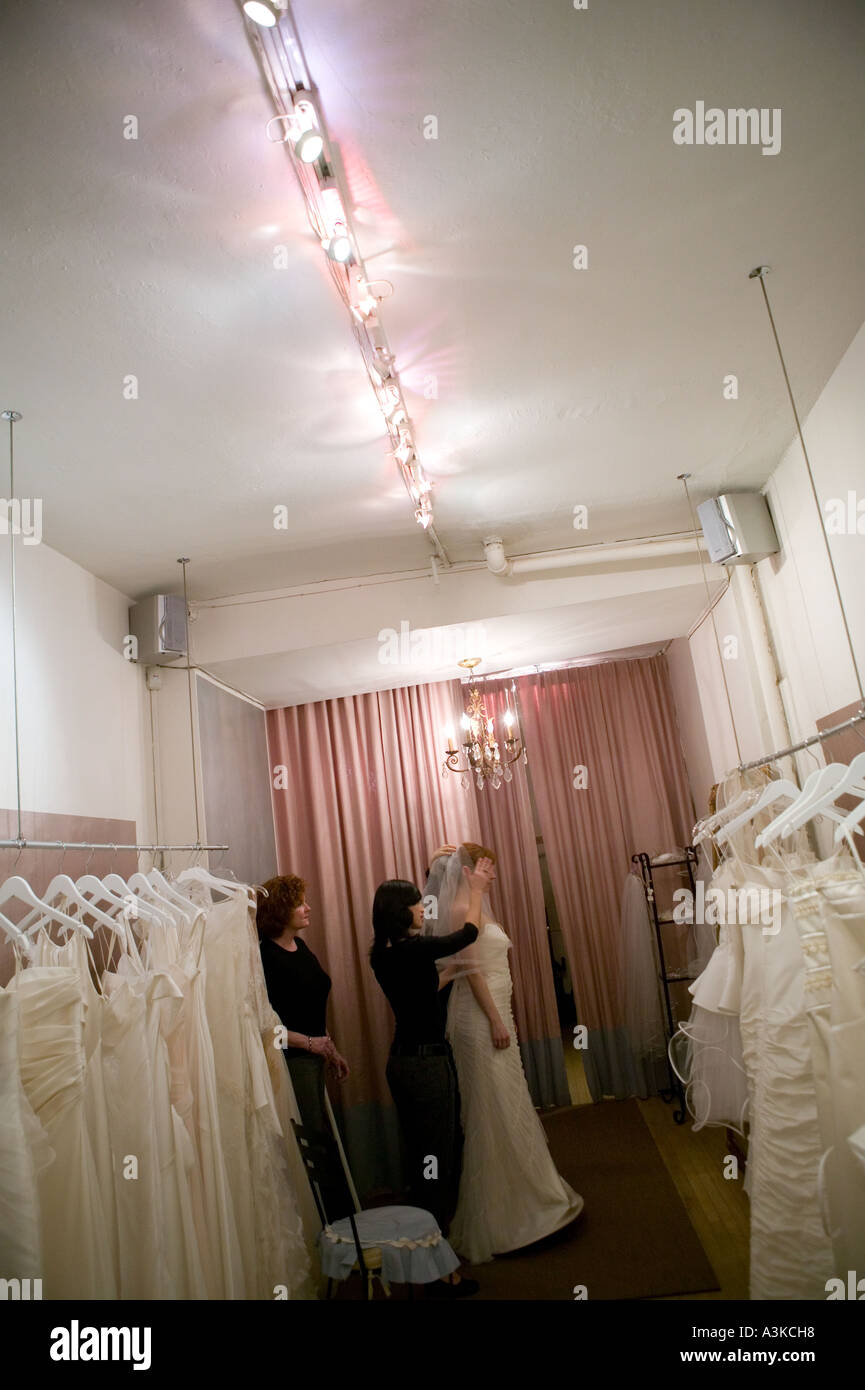 b9f91158907 A young woman looks at herself in a mirror as she tries on a white wedding  dress in a store in New York January 2006