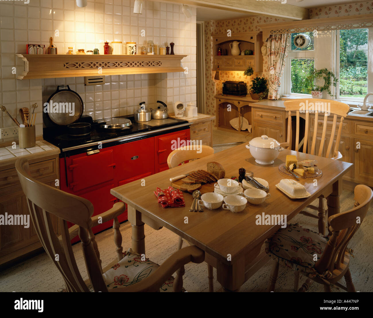 red aga oven in traditional country kitchen with wooden dining table and chairs - Traditional Country Kitchen