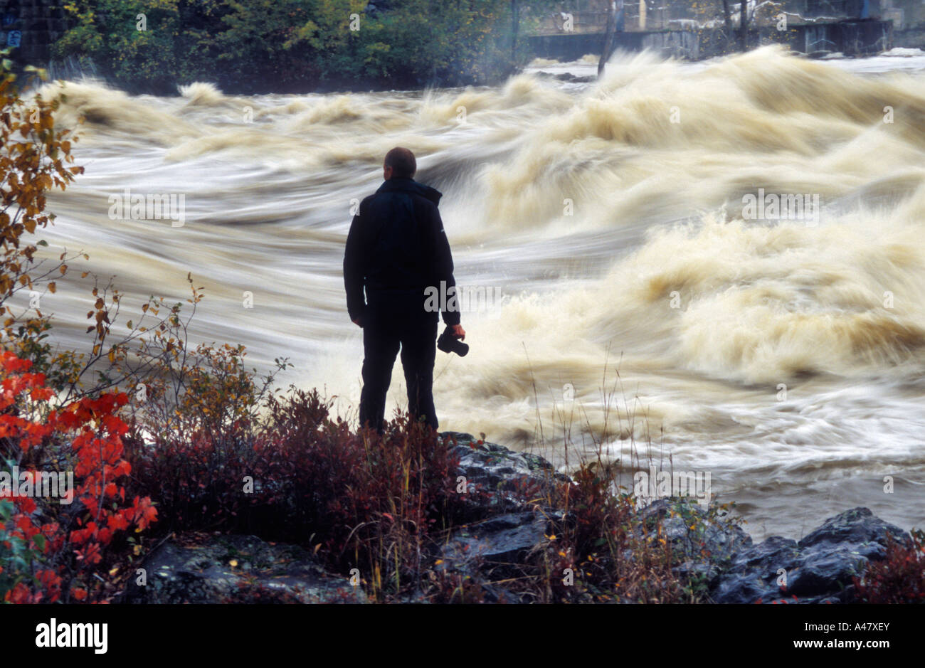 A photographer silhouetted against a river in full flood after autumnal storms Stock Photo