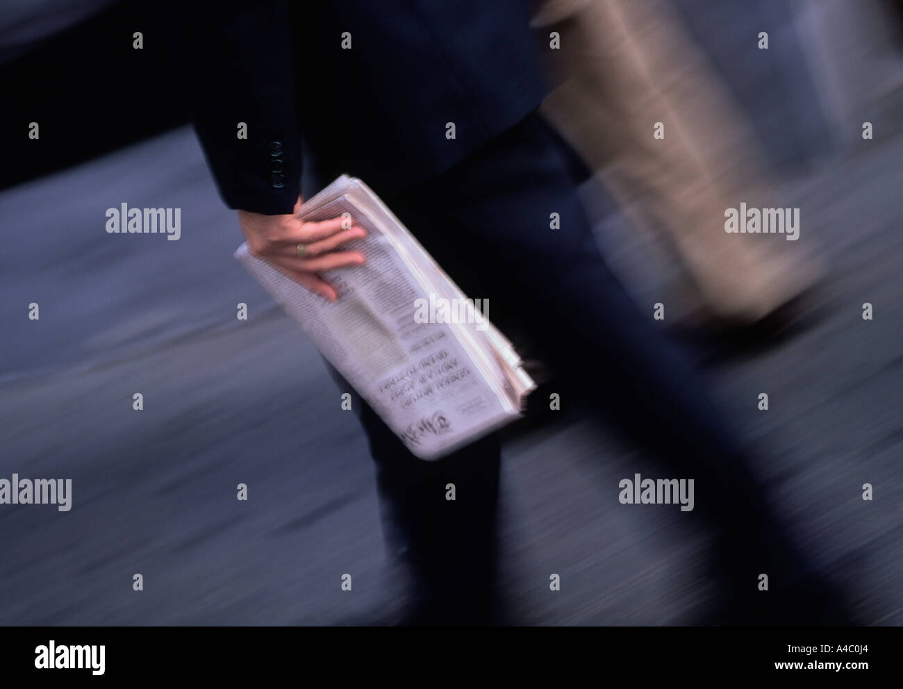 New York City Businessman in a Suit Carrying Newspaper - Stock Image