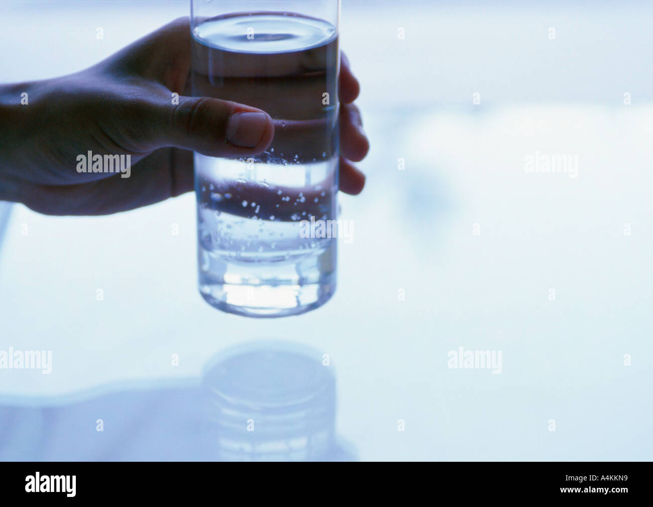 Hand holding glass filled with water, close-up - Stock Image