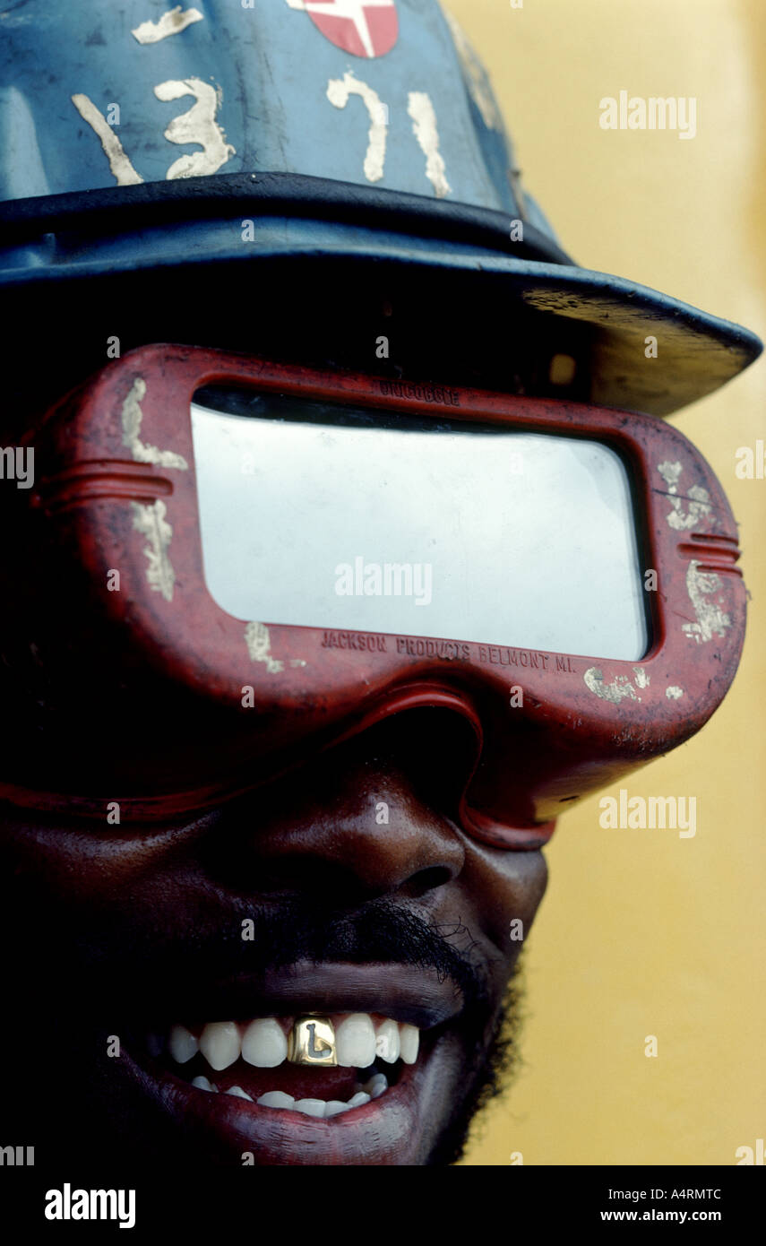 A graphic closeup of a black construction worker's face showing a gold tooth - Stock Image