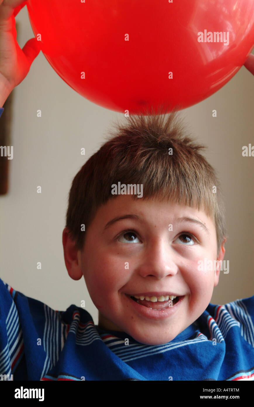 A 7 year old boy holds a red balloon over his head and static electricity pulls his hair towards the balloon Stock Photo