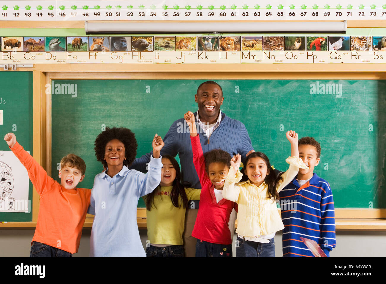 Male teacher and students cheering in classroom - Stock Image