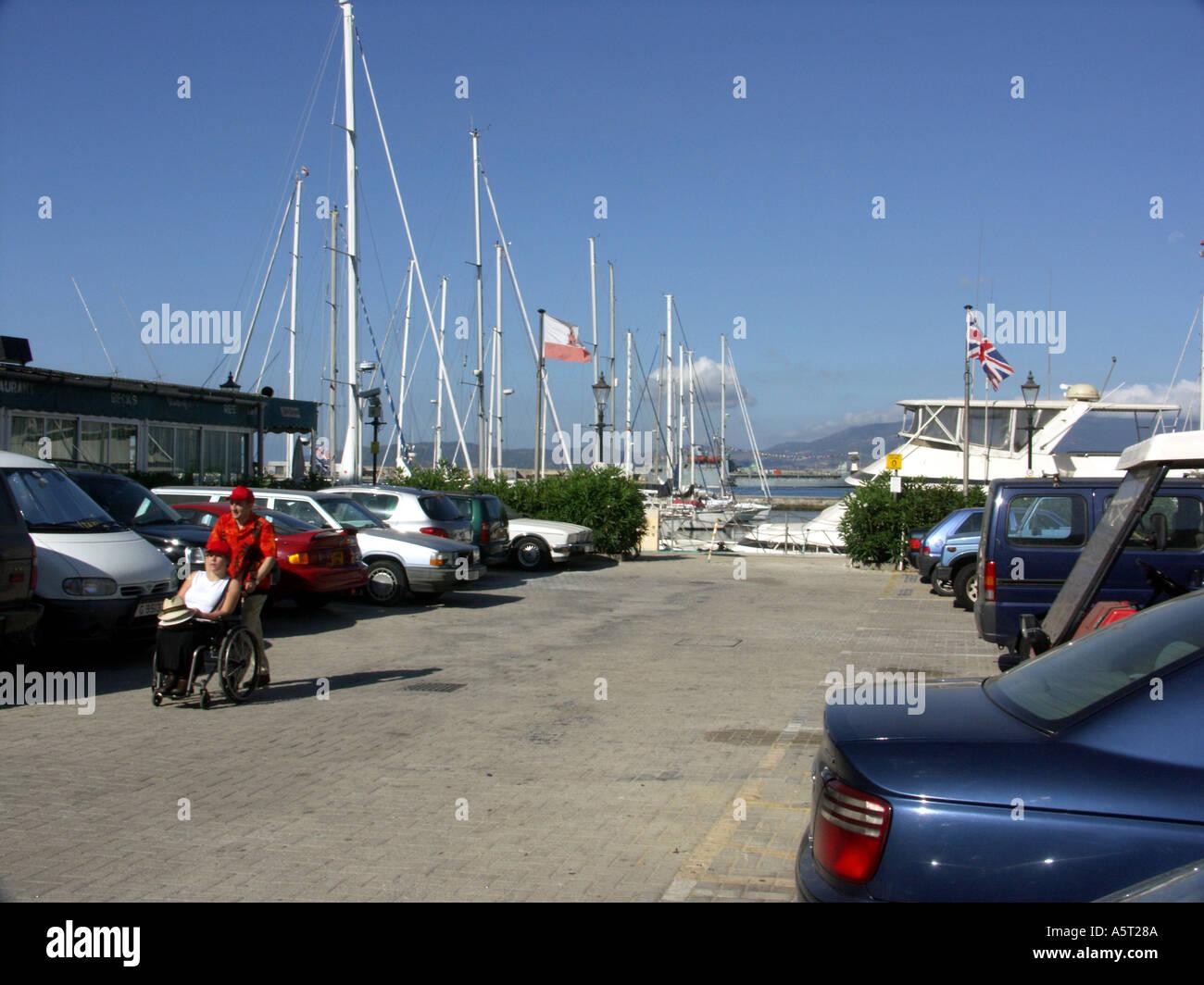Man Pushing Woman in Wheelchair Queensway Gibraltar - Stock Image