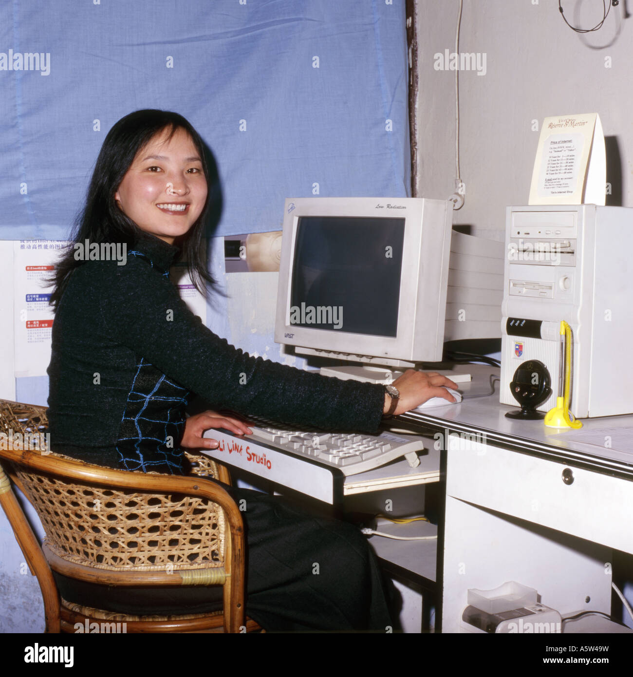 Smiling,pretty,fashionable modern local girl using an internet cafe computer,Dali,Yunnan Province,China. Stock Photo
